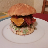 Hamburguesa rellena de queso con costra de mostaza.